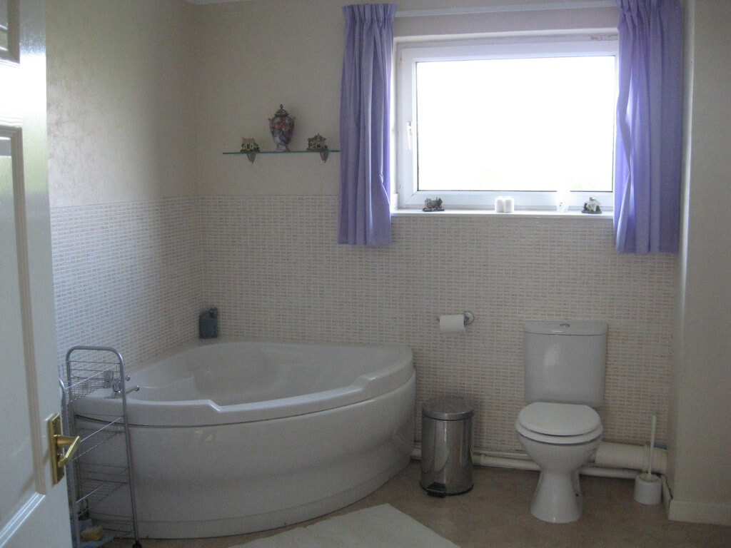 The large bathroom has a corner bath and separate walk in shower