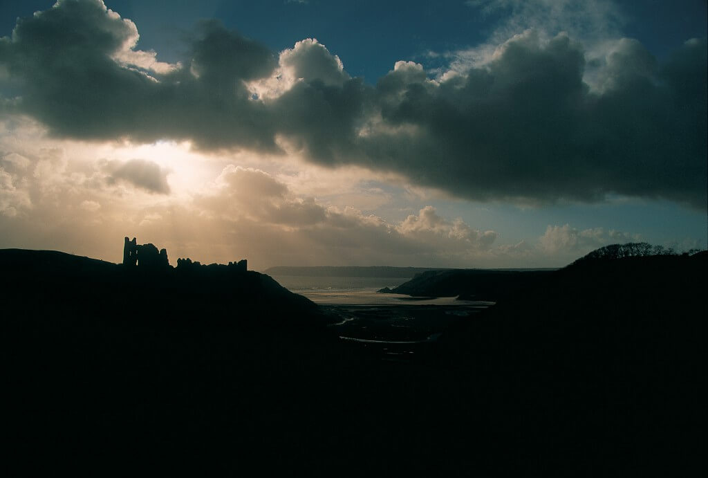 Sun breaking through the clouds over Pennard Castle near Three Cliffs Bay
