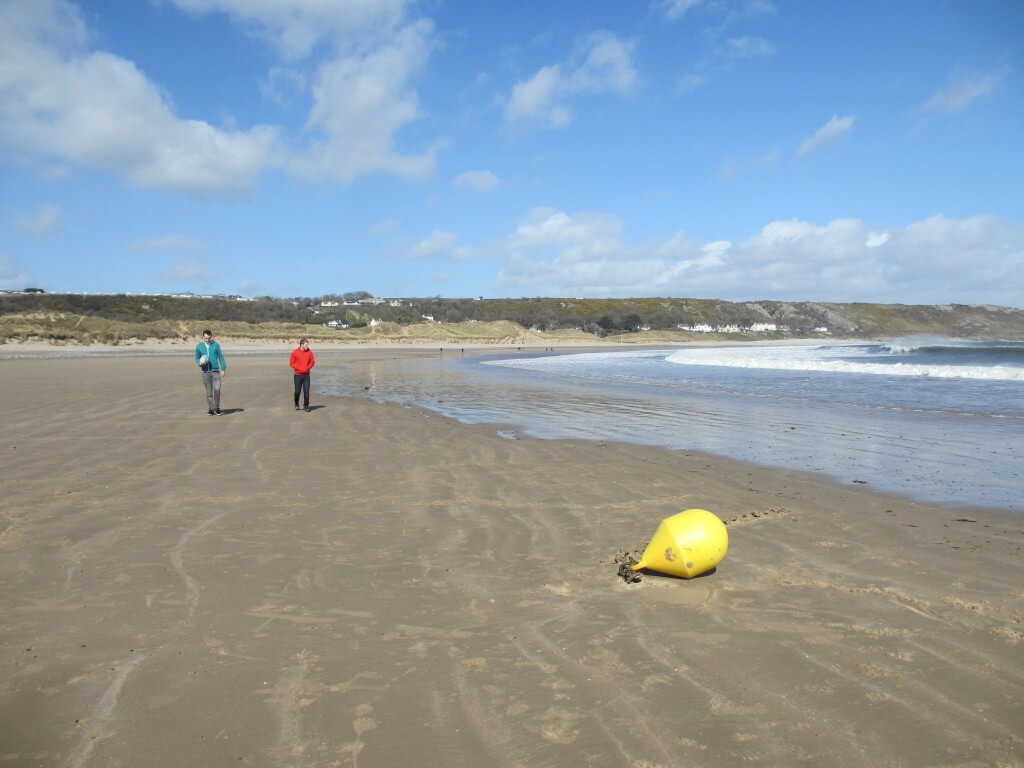 Empty beach with two people walking towards a buoy.